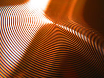 Bronze copper vertigo circles grooves rings. Photo of gold bronze copper vertigo circles rings grooves with light dancing and being refracted off its surface Stock Image
