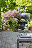 Bronze Cranes in Japanese Inspired Garden. Bronze Cranes Sculpture in Japanese Inspired Zen Garden with Pagoda and Waterfall Royalty Free Stock Photo