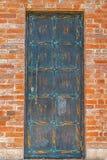 Bronze dörr i tegelstenväggen Arkivbild