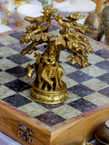 Bronze decorated chess piece. Bronze chess piece showing the lord krishna sitting under a tree and playing the flute Royalty Free Stock Image
