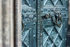 Bronze door with antique brass knocker in the shape of a lion head royalty free stock image