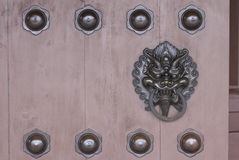 Bronze dragon head knocker decorated on the wooden gate Royalty Free Stock Image