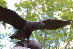 Bronze eagle taking off a stone monument Stock Photos
