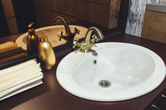 Bronze faucet in the bathroom washstand Royalty Free Stock Photos