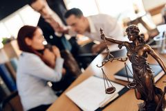 Bronze figurine of Themis holds wedding rings on scales of balance, being in foreground. stock photos