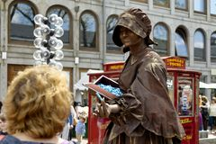Bronze fortuneteller. Boston, Massachusetts USA - 2013 - Woman wearing bronze colored makeup and clothing moving as a mechanical fortune teller,  trading Royalty Free Stock Photos