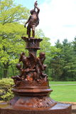 Bronze fountain. Sweet cherub blowing his horn while boys play with swans as the water trickles over them Royalty Free Stock Photo