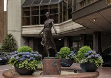 Bronze girl with a rose sculpture in front of the entrance to the Rittenhouse Hotel, Philadelphia, Pennsylvania. Pictured is a bronze sculpture of a young girl stock photography