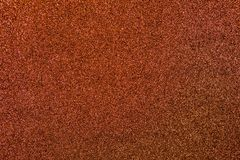 Bronze Glitter Background. Reddish bronze colored sand paper textured background with sparkles and glitters royalty free stock image