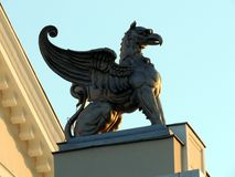 Bronze griffin statue at sunset. Bronze griffin statue on top of the Theater building in Drobeta Turnu Severin, Romania. The picture was taken at sunset in the Stock Photo