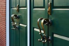 Bronze handles cast shadows on the green door 2011.02.04 royalty free stock photos
