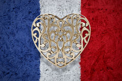 Bronze heart on France flag in background stock photos