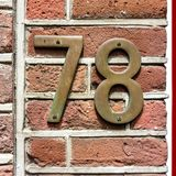 Bronze hous number seventy eight 78. On a brick wall Stock Photography