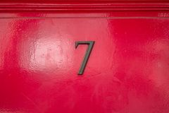 Bronze house number 7. Bronze house number seven 7 on a red door Royalty Free Stock Photo