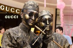 Bronze imitation of reality show, wearing a hundred years before the Chinese Qing Dynasty costumes and smoking gun. In the modern large-scale shopping malls royalty free stock photos