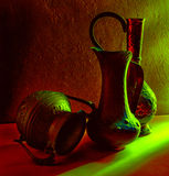 Bronze jugs against a concrete wall Royalty Free Stock Photo