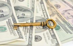 Bronze key on background of dollar bills. Stock Image