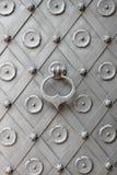 Bronze knocker. On a metal door royalty free stock image