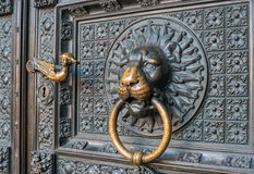 Bronze knocker in the shape of a lion`s head at the gate of the Cologne Cathedral, the most famous church in Germany. Royalty Free Stock Photos