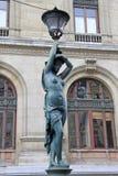 Bronze lamppost shaped as antique caryatide near Palais Garnier, the Paris Opera House in Paris, France. Bronze lamppost as caryatide near Palais Garnier, the Royalty Free Stock Photo