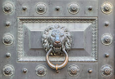 Bronze lion. Handle antique bronze door in the form of head of a lion on a ring stock photo