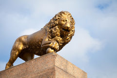 Bronze lion with ball, monument on stone base Royalty Free Stock Photography