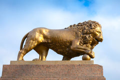 Bronze lion with ball, monument on stone base Royalty Free Stock Images