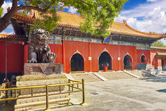 Bronze lion at the entrance to beautiful Yonghegong Lama Temple. Royalty Free Stock Photo