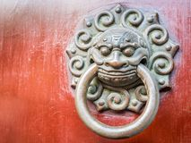 Bronze lion head door knocker. In traditional Chinese design style. Weathered cracks in red wooden backing stock photography