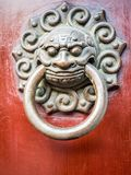 Bronze lion head door knocker. In traditional Chinese design style. Weathered cracks in red wooden backing royalty free stock photography