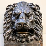 Bronze Lion head on the wall. The head of bronze lion stated on the wall. Outdoors, close up, isolate stock photography