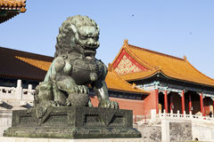 Bronze Lion Statue. A bronze lion statue with it's paw on a ball sits in a courtyard of the Forbidden City in Beijing Stock Image