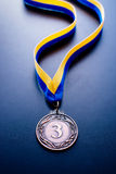 Bronze medal on a blue background. Bronze medal in the foreground on yellow blue ribbon Stock Image