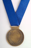 Bronze medal on blue ribbon. Bronze medal with blue ribbon on grey background Royalty Free Stock Images