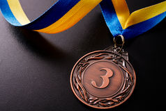 Bronze medal on a dark background Stock Photos