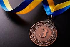 Bronze medal on a dark background Stock Photos