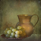 Bronze mug and grapes on grunge background. Vintage and grunge texture with ripe grapes and a golden mug stock photos