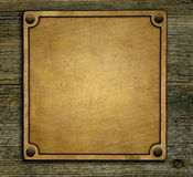 Bronze nameplate. On wooden background Royalty Free Stock Photo