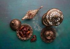 Bronze plate with dates, coffee cup, arabic lantern and aladdin lamp on dark green wooden background. Ramadan kareem. Ramadan