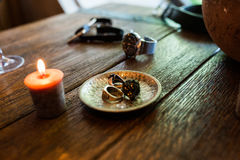 Bronze plate with men's rings in on a wooden table. Royalty Free Stock Photos
