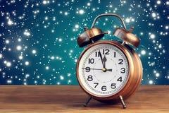 Bronze retro alarm clock at twelve o`clock amid flying snow. Royalty Free Stock Photos