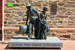 Bronze sculpture in front of the Migration Museum in Adelaide, SA. Bronze sculpture, dedicated to all migrant settlers to South Australia, in front of the royalty free stock photography