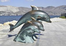The bronze sculpture of three dolphins on the beach.  Stock Photography