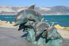 The bronze sculpture of three dolphins on the beach.  Royalty Free Stock Photo