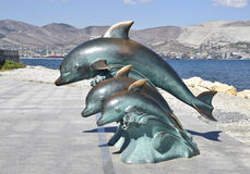 The bronze sculpture of three dolphins on the beach.  Stock Photos