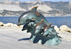 The bronze sculpture of three dolphins on the beach.  Stock Photo