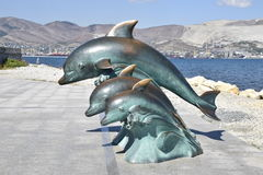 The bronze sculpture of three dolphins on the beach.  Royalty Free Stock Image