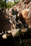 Bronze sculpture and waterfall. Man and woman sculpture with waterfall Royalty Free Stock Photos
