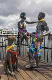 Pobl Fel Ni People Like Us statue at Cardiff Bay Boardwalk, Wales. This bronze sculpture of a young couple and their dog stands in Mermaid Quay. `People Like Us Stock Image