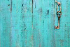 Bronze skeleton key hanging on vintage teal blue wood door. Metal skeleton key hanging from rope on antique green wooden fence Royalty Free Stock Photo